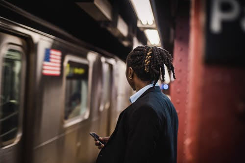 Man in suit looking at arriving train on subway