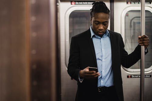African American office worker surfing net on mobile phone while getting home by subway