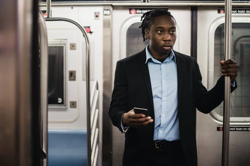 Young black man in suit getting to work by subway
