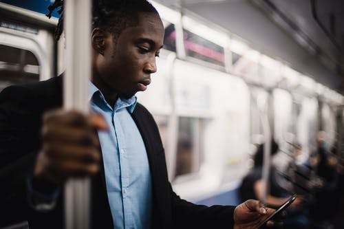 African American office worker using smartphone while commuting by train