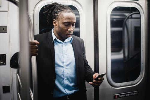 Serious black passenger browsing internet on smartphone on subway train