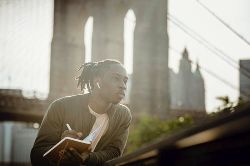 Thoughtful young black man with dreadlocks listening to audio story in wireless earphones and writing down information in notebook while leaning on fence on city promenade