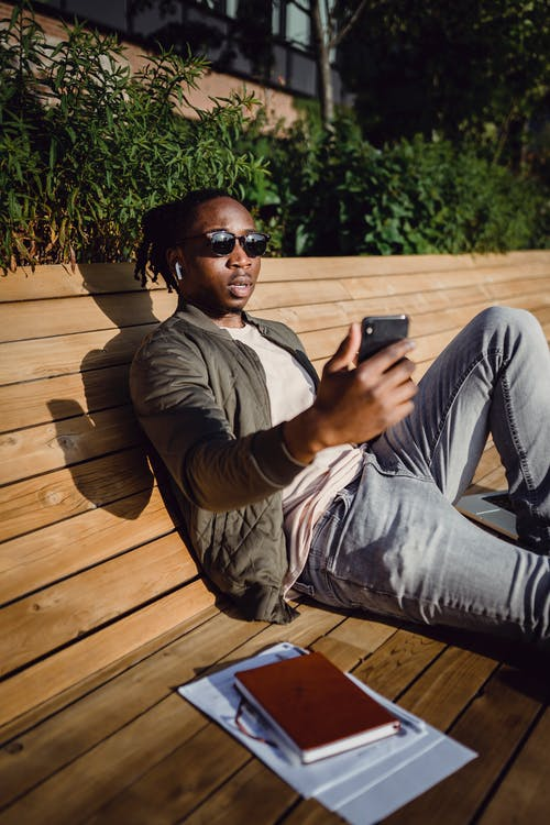 Young black guy chatting on smartphone sitting on wooden bench