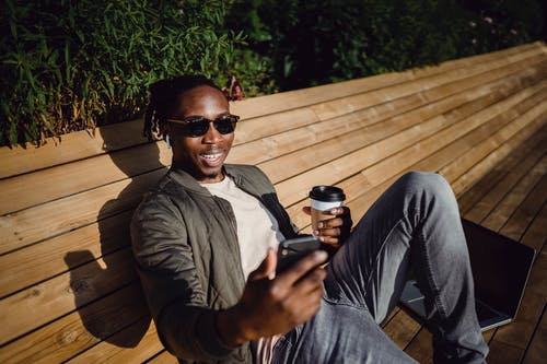 Cheerful young black man having video conversation via smartphone during coffee break in park