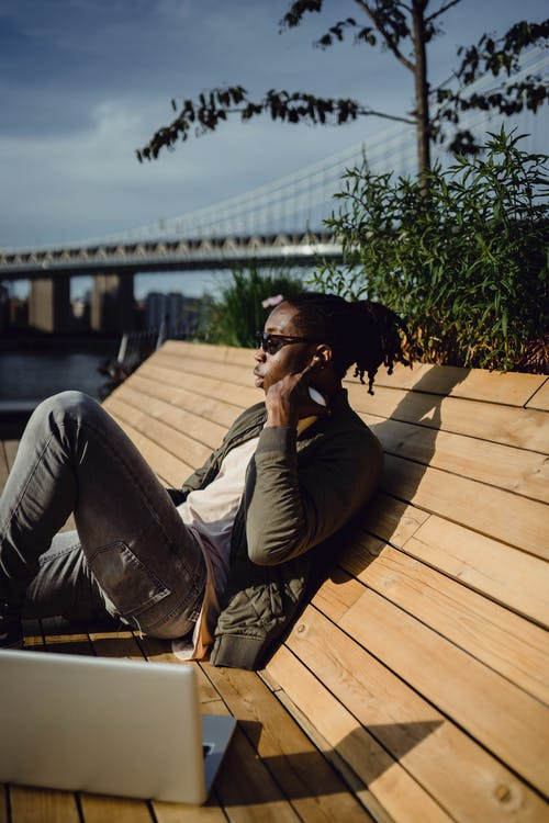 Side view of African American young guy in casual wear and sunglasses chilling on wooden bench with laptop and listening to music in true wireless earphones