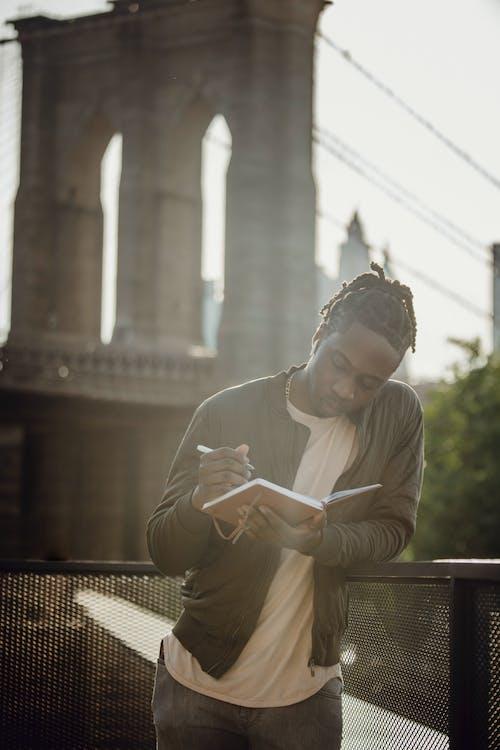 Pensive black man taking notes in diary against bridge