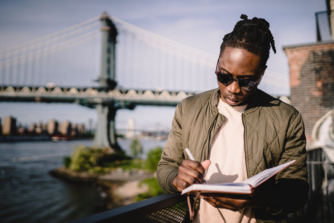 Concentrated young black male checking schedule in notebook while standing on city promenade against bridge on sunny day