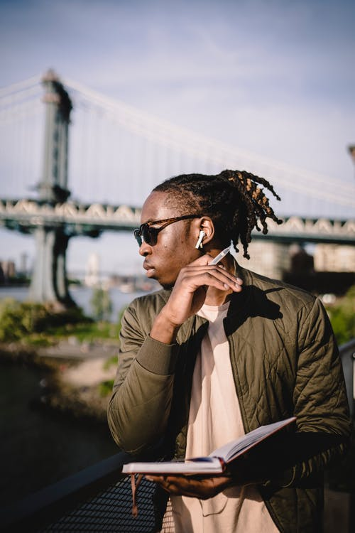 Focused black man waiting for meeting on river embankment