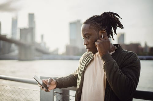 Melancholic black man with smartphone listening to music in earphones