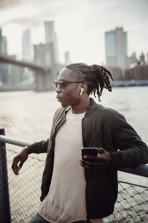 Stylish African American man in casual wear and sunglasses listening to music in wireless earphones while standing leaned on hand near bridge fence with cellphone and looking away