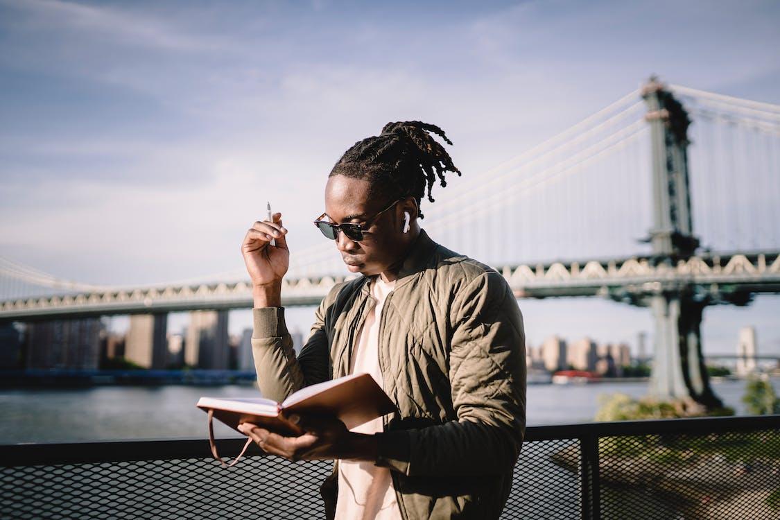 Thoughtful black guy in earphones standing with organizer on bridge