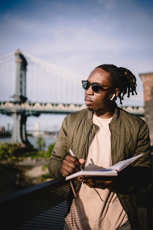 Young African American man in sunglasses listening information through wireless earphones and writing notes in notebook at sunny day