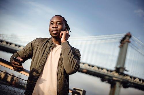 African American man calling on smartphone through earphones