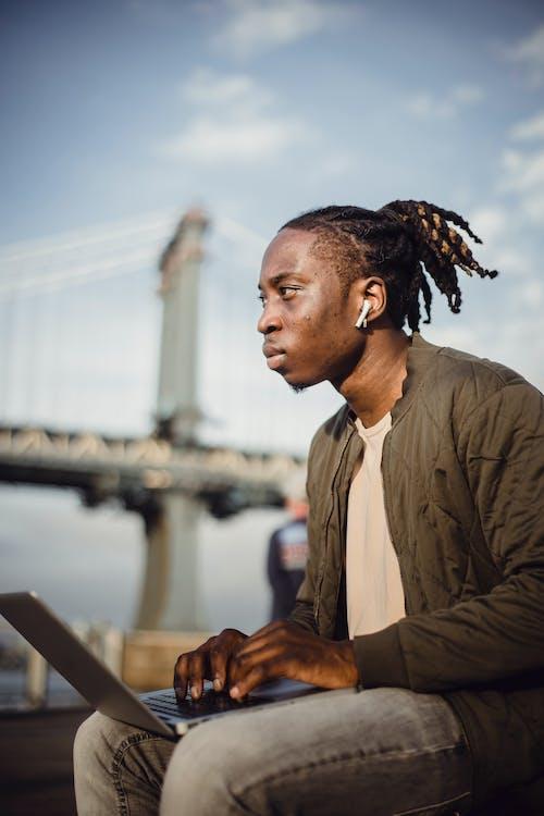 Focused black male worker typing on laptop