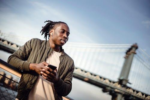 Gratis stockfoto met Afro-Amerikaans, afspeellijst, andere kant op kijken, apparaat