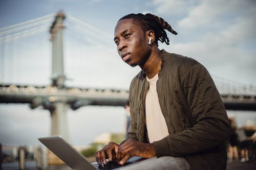 Low angle of concentrated black male freelancer working in city park while typing on keyboard and looking away