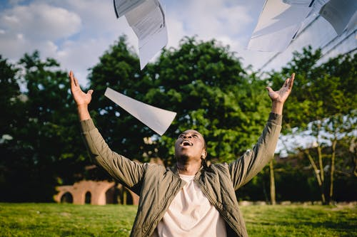 Cheerful young African American male student in casual clothes throwing college papers up in air while having fun in green park after end of exams