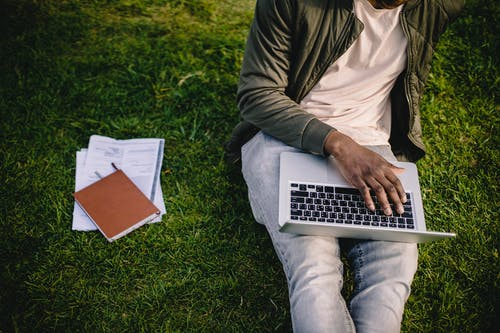 Crop black student with laptop and papers on green lawn