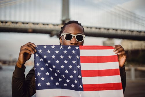 Young African American male with American Flag bandana against bridge