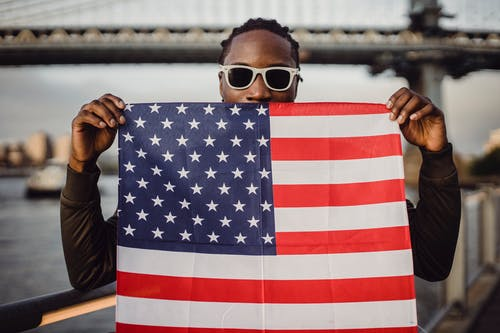 Positive African American male with American flag kerchief in hands