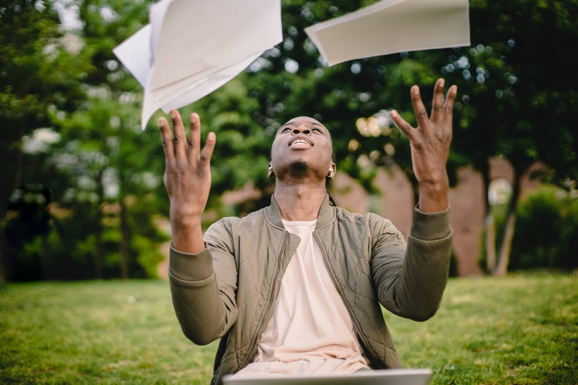Content black remote worker throwing work papers in air happy to get rid of boring paperwork while sitting in green park with laptop