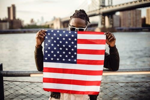 Black man holding American flag on city river embankment