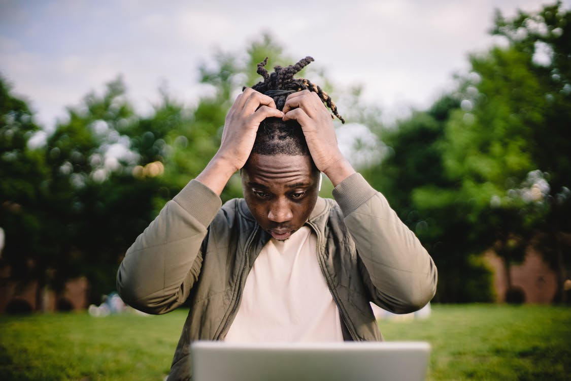 Stressed black male entrepreneur working on laptop in park