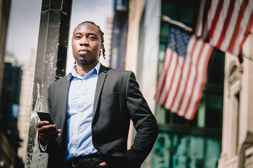 Low angle of serious well dressed ethnic male manager leaning on metal pillar on street and using cellphone against government building with hanging American flags