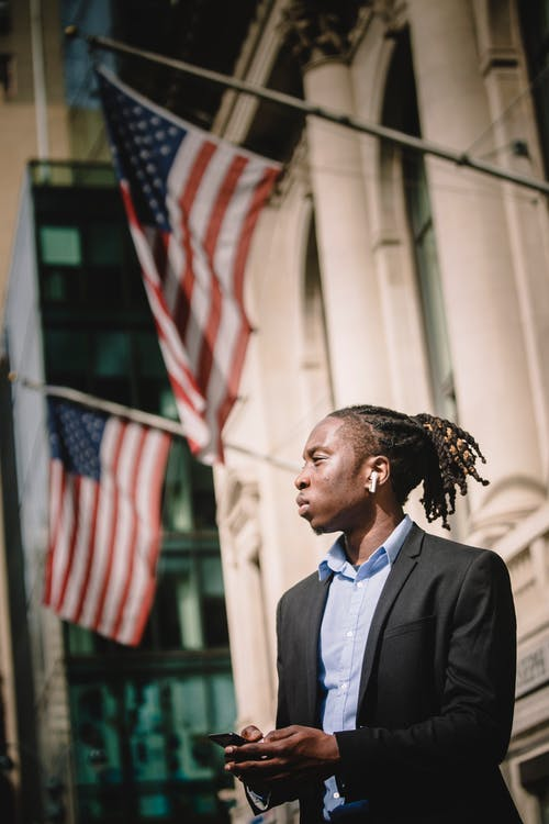 Pensive ethnic male manager standing next to building with American flags and browsing smartphone