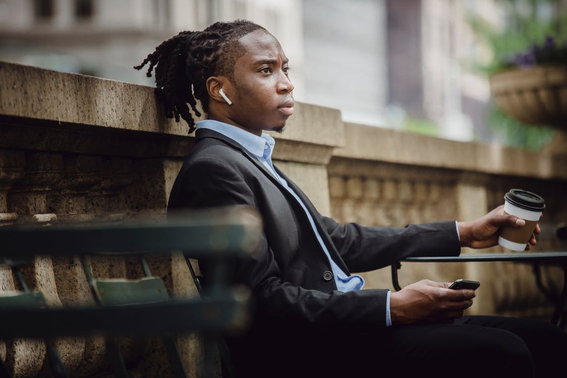 Thoughtful black businessman in wireless earphones with smartphone and coffee to go in cafe