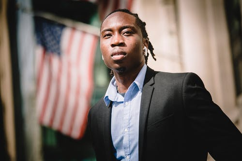 Serious black businessman against blurred building with American flags