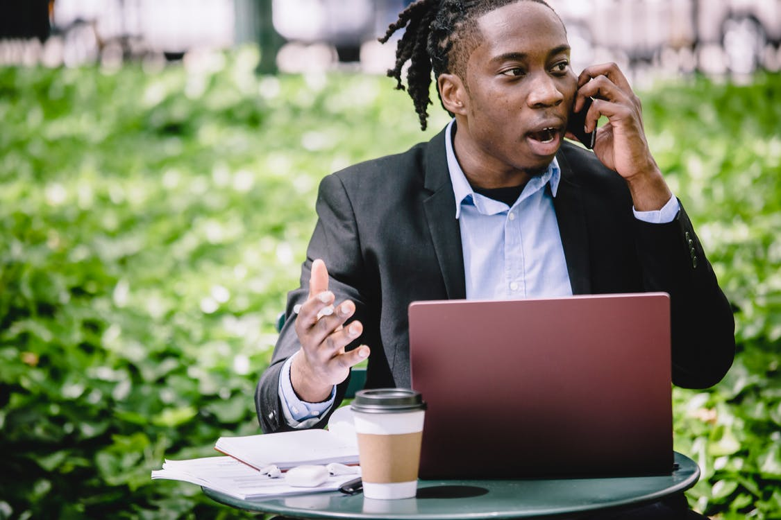 Young African American male entrepreneur in smart suit sitting in outdoor cafe with laptop and arguing on cellphone on sunny day
