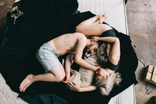 Couple Sleeping With Pet Dog