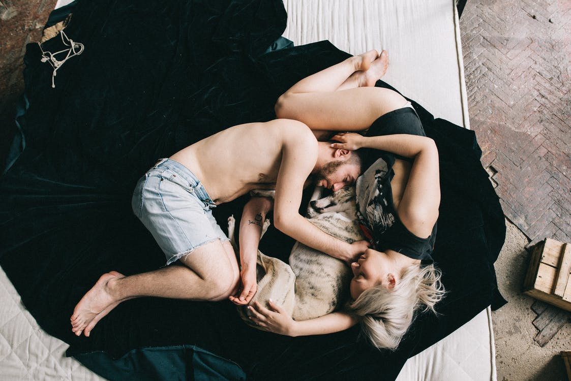 Couple Sleeping With Pet Dog