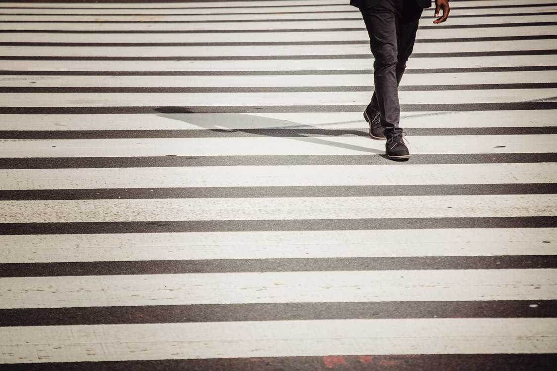 Crop anonymous black person in black trousers and shoes walking on zebra crossing in sunlight