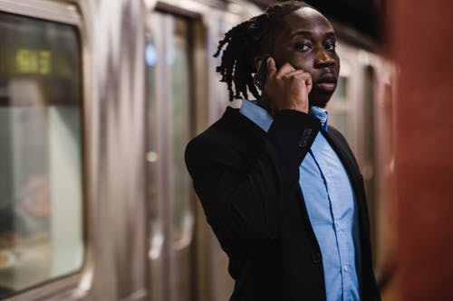 Young African American office worker in formal suit making phone call while standing in subway and waiting for train