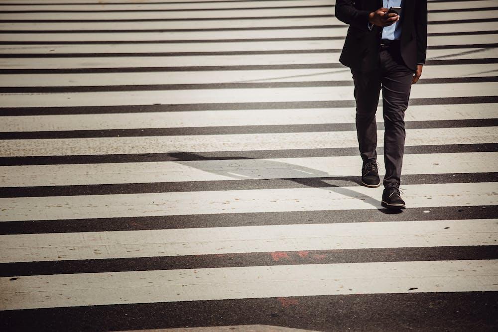 A man walks across the crosswalk.   Photo: Pexels