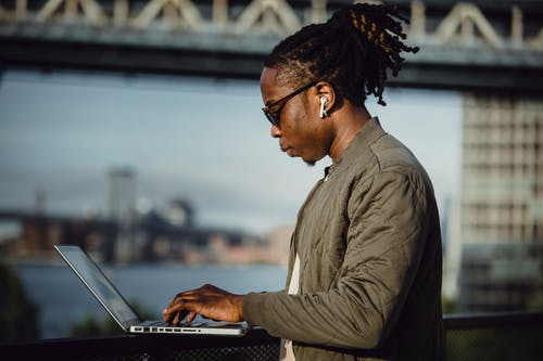Young focused freelancer using laptop and listening to music
