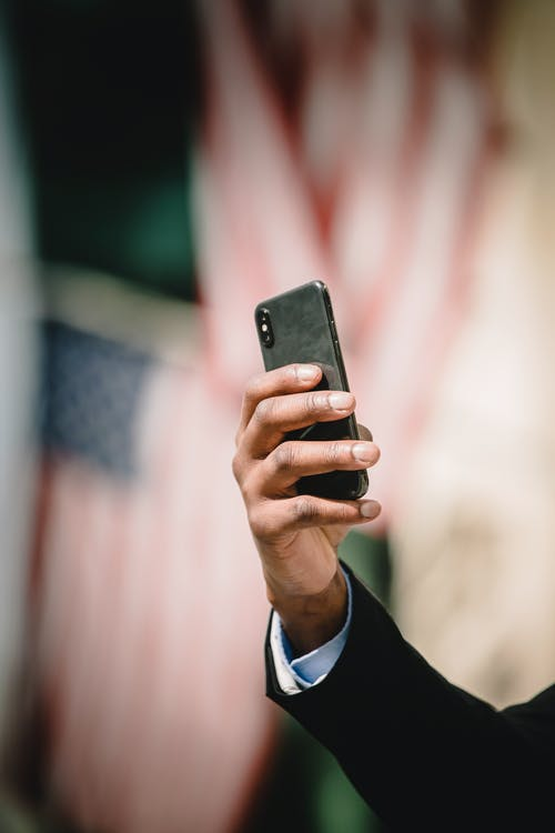 Crop anonymous office worker in formal suit using cellphone against blurred background of American flags