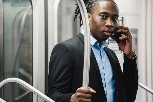 Male commuter in formal wear talking on phone on train