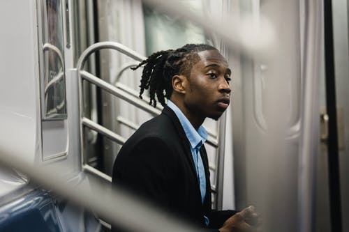 Side view of young stylish black man in formal wear with dreadlocks sitting on train seat and looking away with expression of slight interest on face