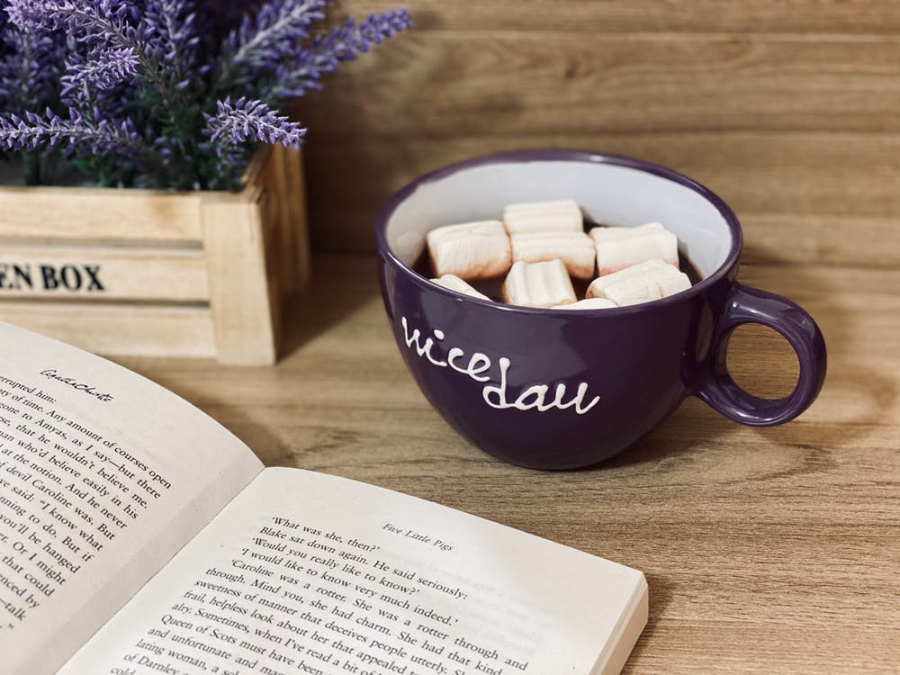 White Book Page Beside Black Ceramic Mug on Brown Wooden Table