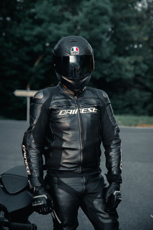 Man Wearing a Leather Jacket and a Black Helmet
