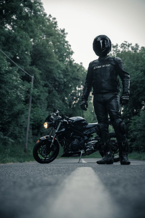 Man in Black Riding Suit Standing Near His Motorbike