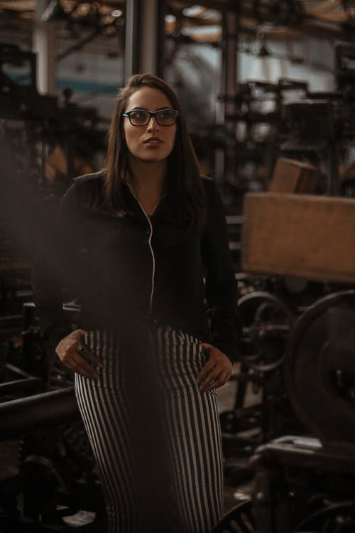 Woman in Black Jacket and Black and White Striped Pants Wearing Black Framed Eyeglasses