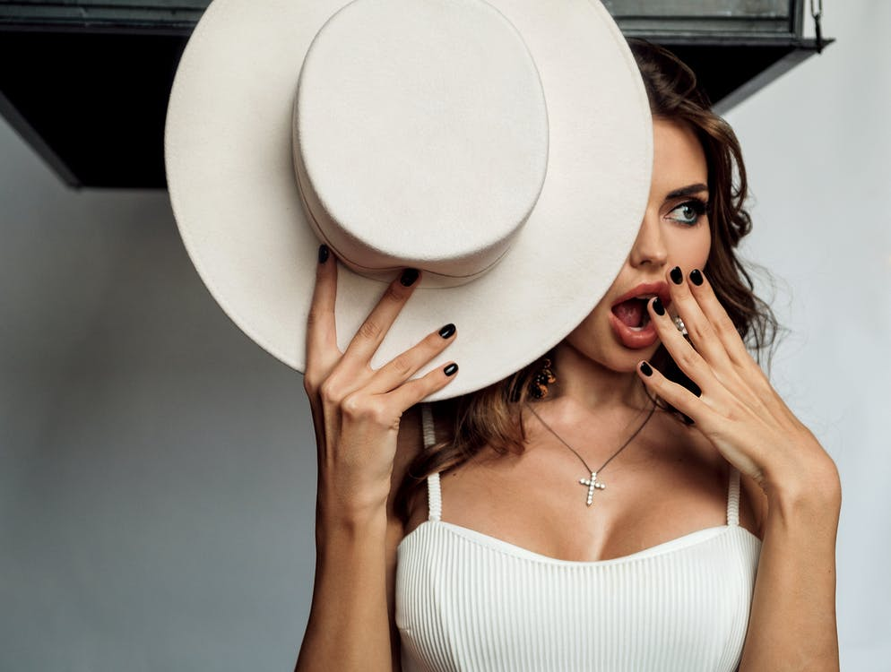 Shocked stylish female with opened mouth and hat in hand standing near white wall and looking away