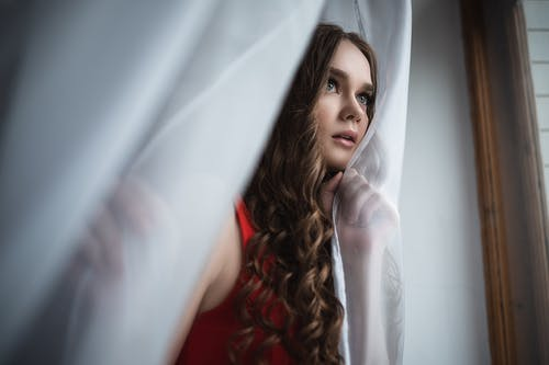 Thoughtful young woman standing near curtains
