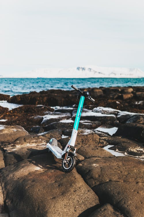 White and Blue Bicycle on Rocky Shore