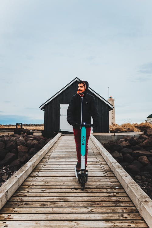 Man in Black Jacket and Black Pants Standing on Wooden Dock
