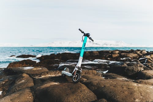Blue and Black Bicycle on Rocky Shore